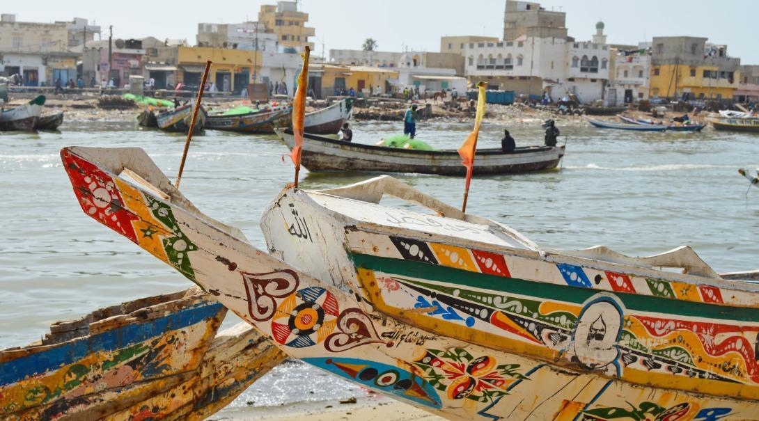 Färgglada fiskebåtar i hamnen i Saint Louis, Senegal som är en destination dit volontärer kan åka i Afrika.